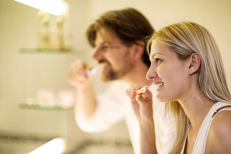 Couple brushing teeth to avoid tooth decay